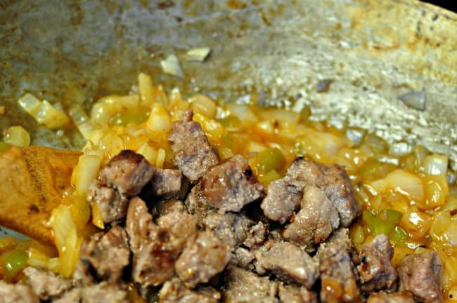 adding meat to sauce in sweet and sour beef or pork