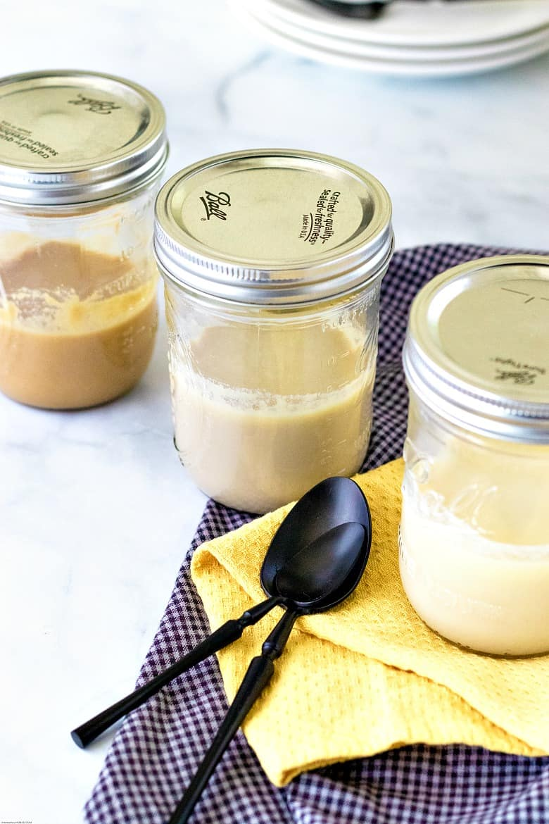 Homemade Sweetened Condensed Milk shown in mason jars with spoon and towels.