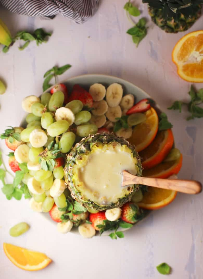 Overhead view of fresh fruit around a pineapple shell filled with fruit dip.