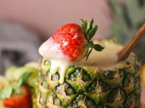 Close up of a strawberry with fruit dip recipe dripping from it on edge of a pineapple shell.