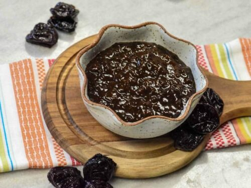 Closeup of Prune Plum Ketchup in bowl on bread board and prunes around it.