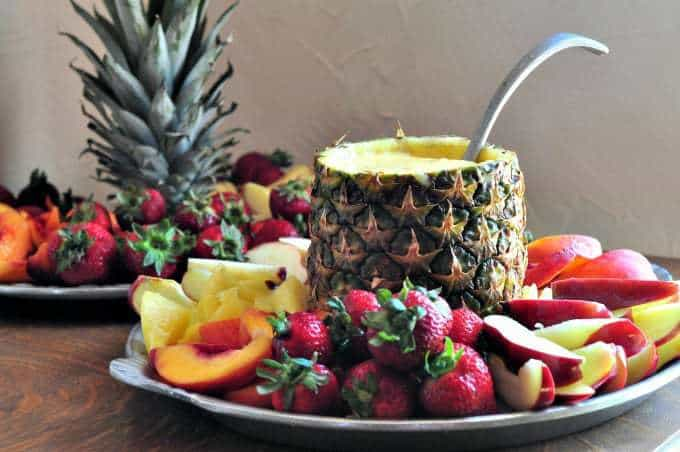 A pineapple filled with an orange fruit dip recipe and surrounded by fresh fruit