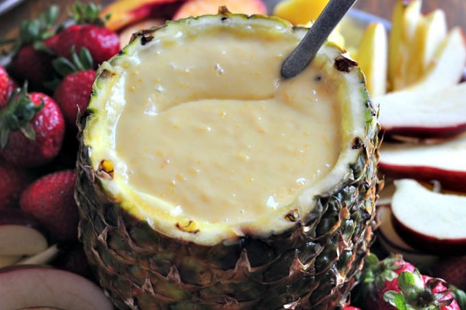 A close up of an orange fruit dip recipe serve in a hollowed out pineapple
