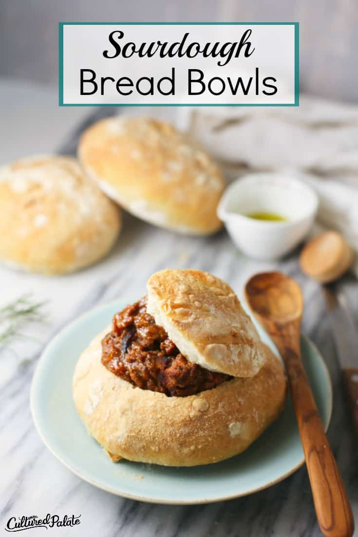 Sourdough Bread Bowls show filled with soup on plate with wooden spoon and text overlay.