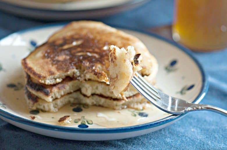 Sourdough Pancakes shown stacked on a plate and a bite on a fork