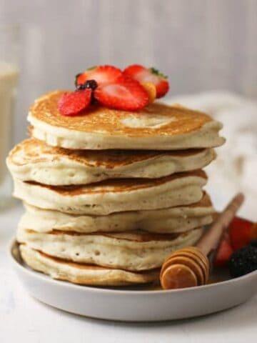 Horizontal image of Sourdough Pancakes on a white plate topped with fruit and honey.