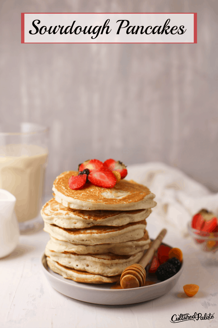 Sourdough Pancakes on white plate with milk in background and text overlay.
