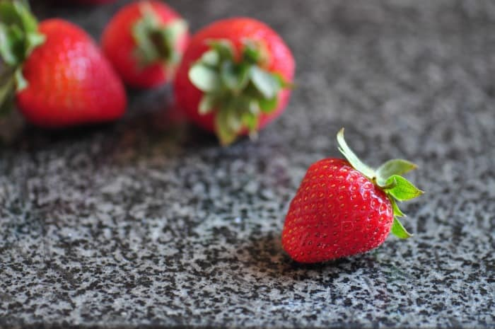A close up of strawberries uses to top homemade cottage cheese