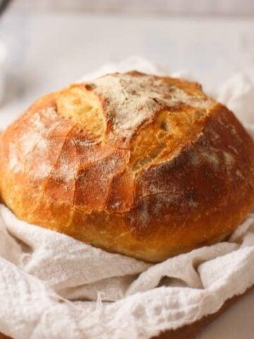 Basic Sourdough Bread shown on tea bowl and cutting board.