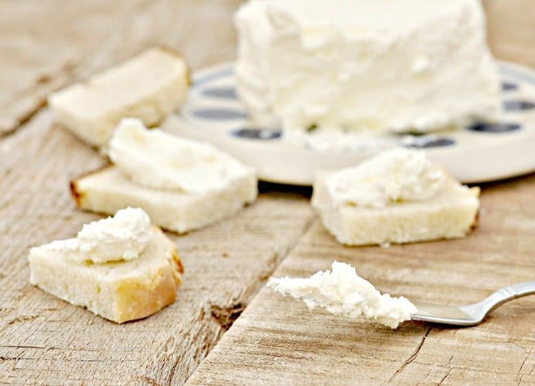 How to Make Cream Cheese - Homemade Cream Cheese shown on knife and chunks of bread