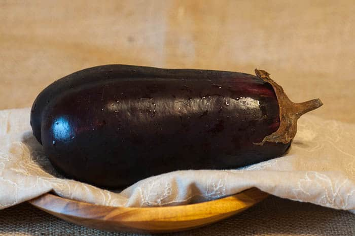 A photo of an eggplant on a table to make eggplant lasagna