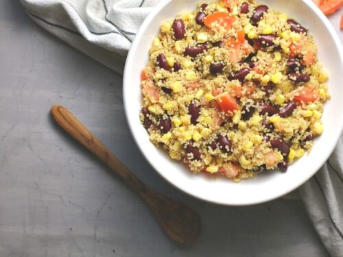 Easy Quinoa salad shown in a white bowl with wooden spoon.