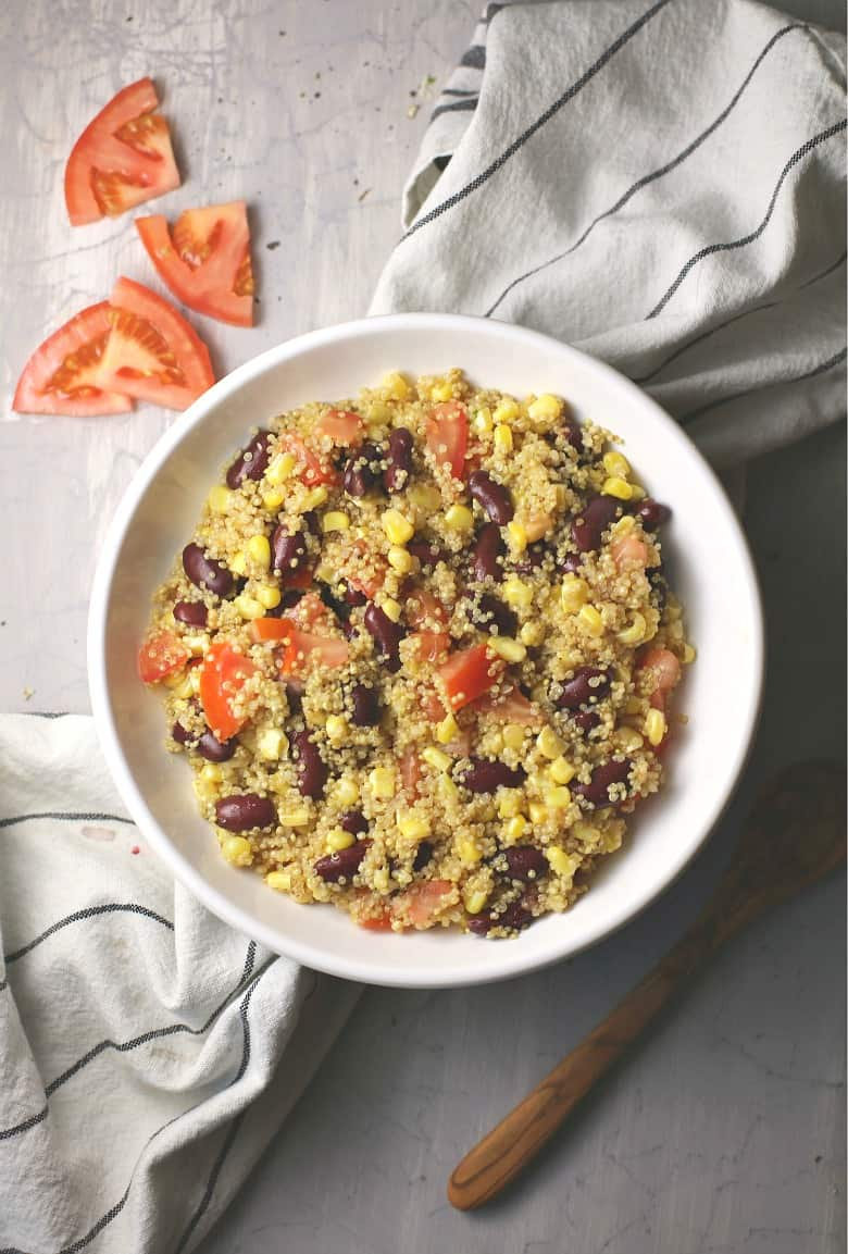 Easy Quinoa Salad recipe shown made in a white bowl on a striped towel with tomatoes to the side.