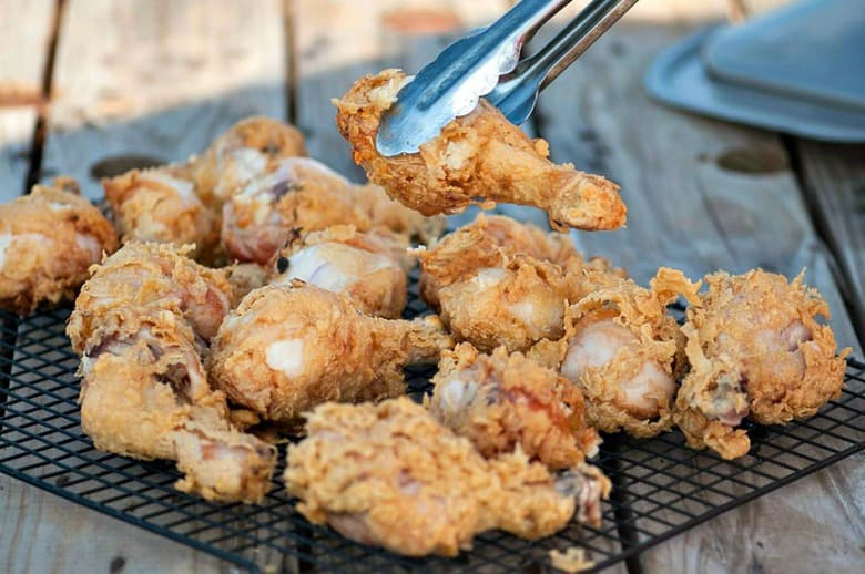 A photo of a pair of tongs picking up fried kefir battered chicken