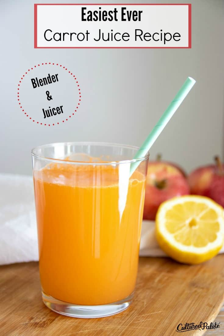 Glass of carrot juice recipe with straw and apples and lemons in background.