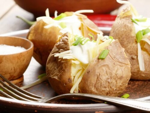 Baked Potatoes in Crock Pot shown in closeup image with fork on a plate.
