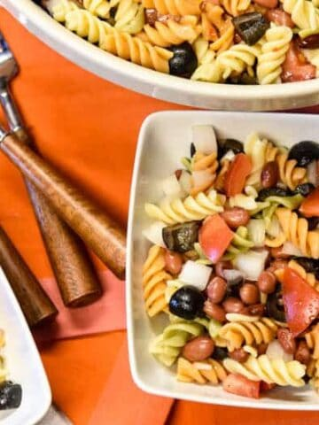 Simple Pasta Salad Recipe shown served in two white bowls and forks with serving bowl filled with salad in background