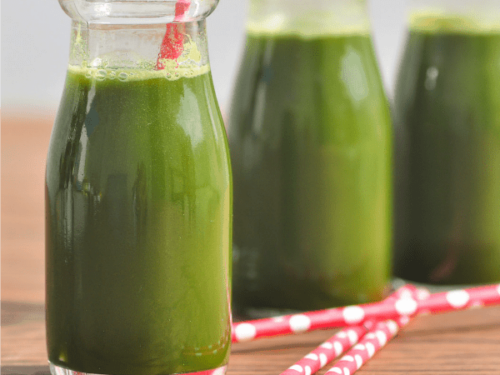3 glasses of green juice on a wooden worktop