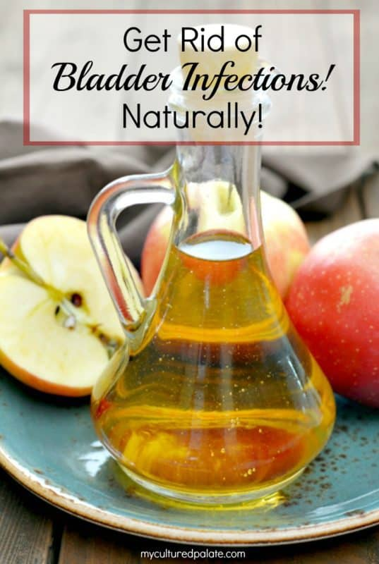 Apple Cider Vinegar from the post How to Get Rid of Bladder Infections Naturally shown on a plate with apples around on wooden table.