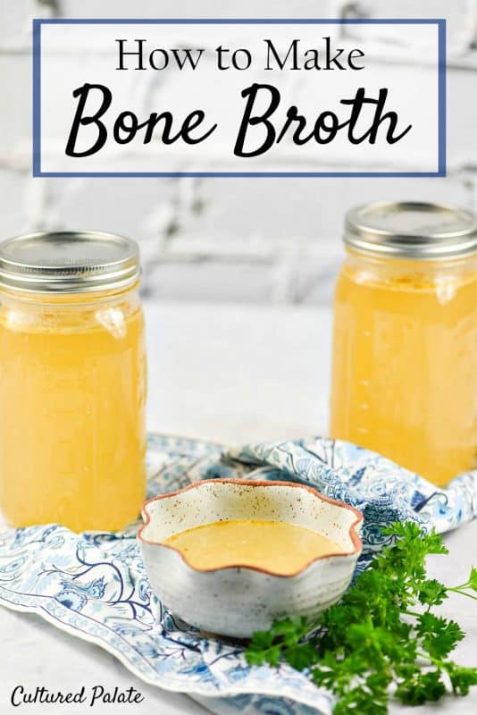 A photo of two glass jars filled with homemade bone broth sitting on a white surface