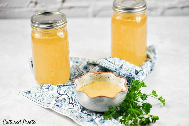 Two glass jars of homemade bone broth on a white counter top