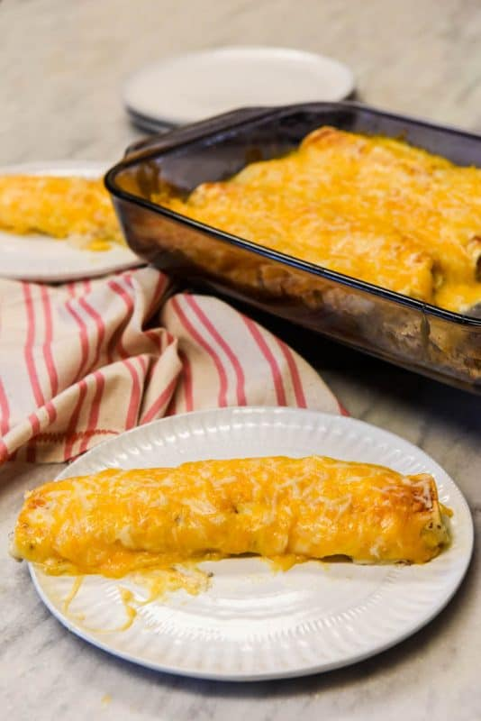 Easy Chicken Enchiladas Recipe shown baked and ready to eat on a plate