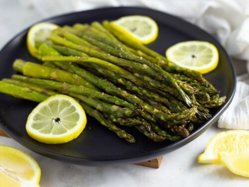 Oven Roasted Asparagus shown on black plate surrounded by lemon slices.