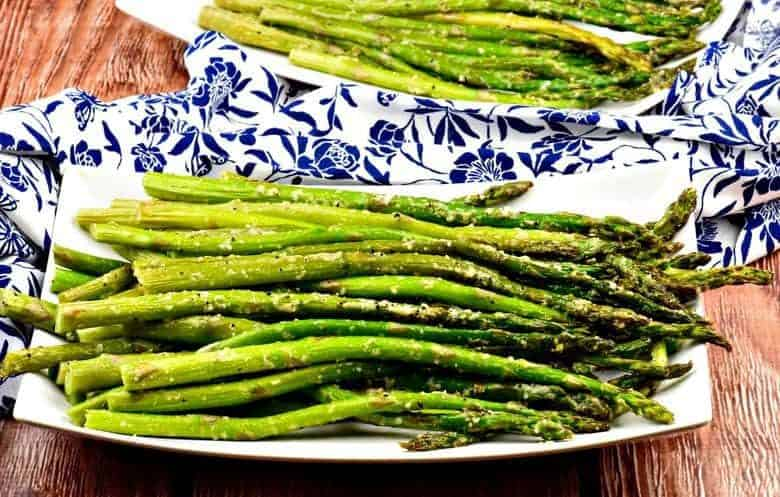 A photo of Oven Roasted Asparagus on a white serving plate