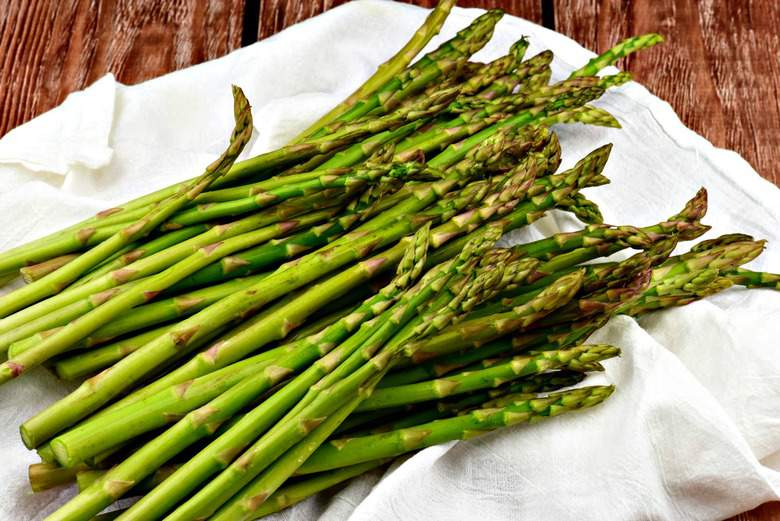 A photo of fresh asparagus laying on a white surface ready to be oven roasted
