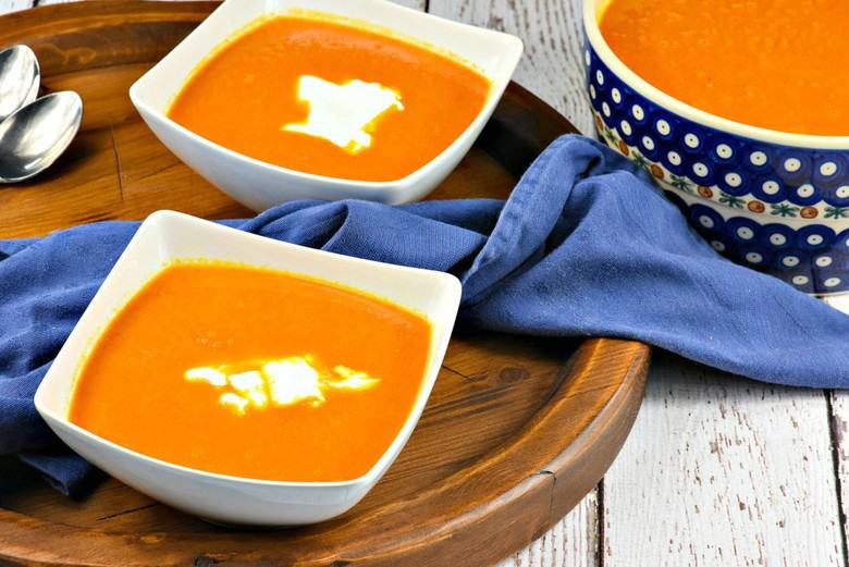 Two bowls of Moroccan Carrot Soup on wooden serving tray
