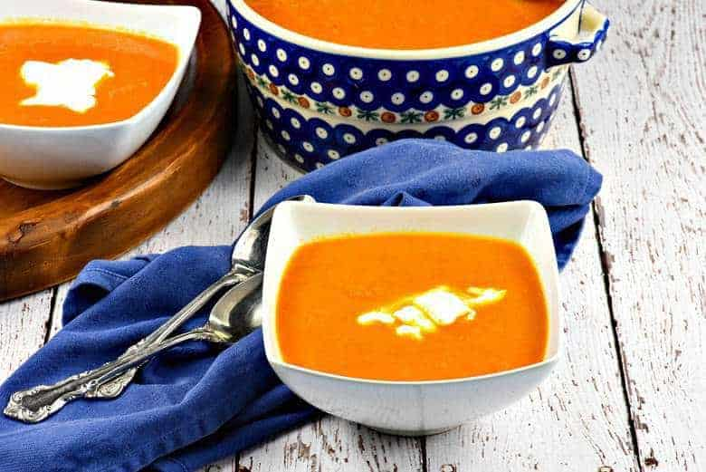 Moroccan Carrot Soup in a white bowl with two bowls in the background