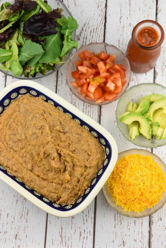 Homemade Refried Beans Recipe shown with lettuce, tomatoes, avocado and cheese