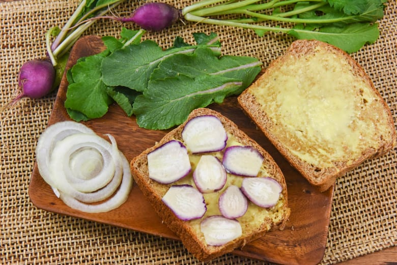 An open radish sandwich on a chopping board with slices of onion and radish tops