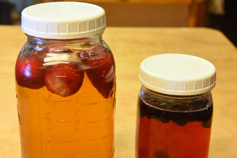 A close up shot of flavoring kombucha with strawberries and grapes
