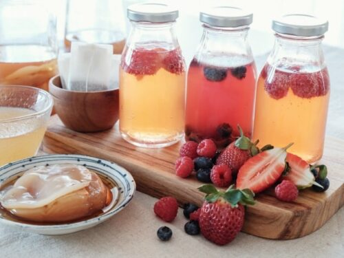Flavored Kombucha shown in jars with fruit and scobby around.
