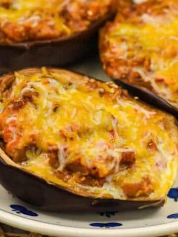 Three stuffed eggplant on a small white plate