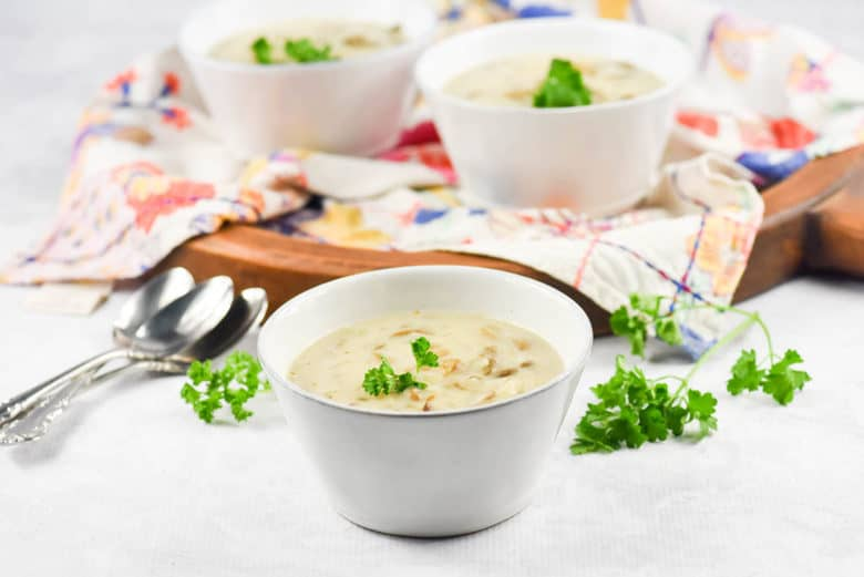 Homemade cream of mushroom soup recipe in a white bowl garnished with parsley