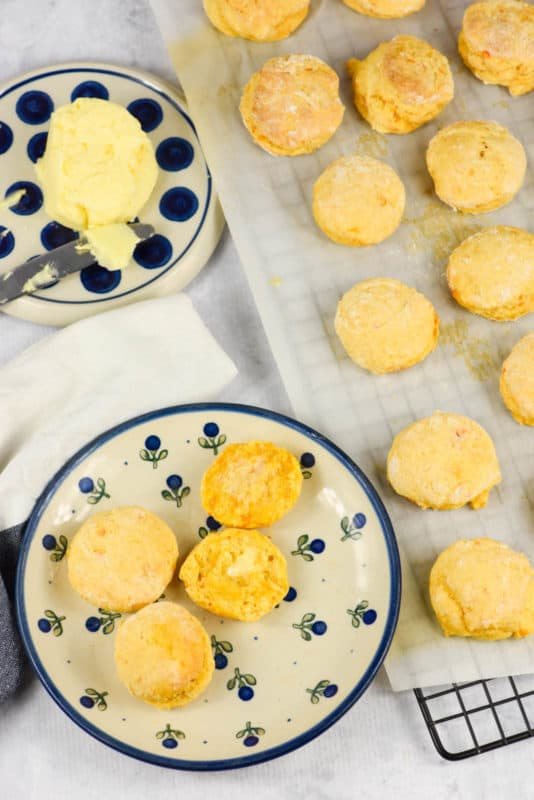 An overhead shot of Sweet Potato Biscuits on a blue and white plate with butter