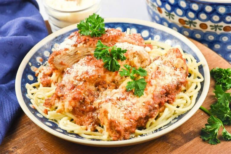 A close up of Crock Pot Chicken Parmesan on a white and blue plate garnished parsley