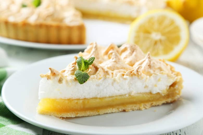 A piece of Lemon Meringue Pie made from Grandma's Lemon Meringue Pie Recipe shown on a white plate