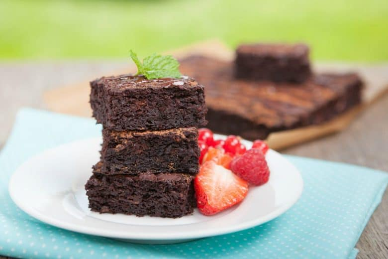 A photo of three coconut flour brownies stacked up on a white plate