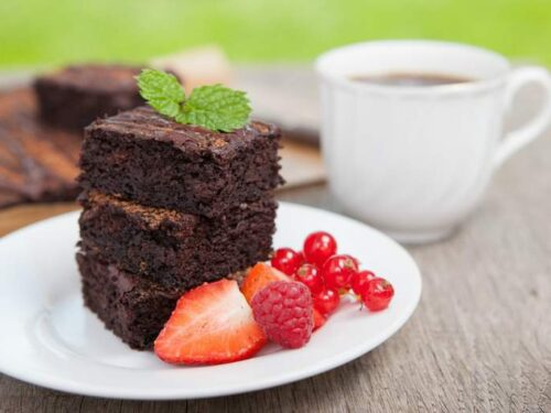 Three coconut flour brownies on a white plate