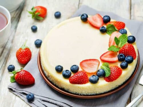 An overhead shot of Sour Cream Cheesecake topped with berries on a wooden surface