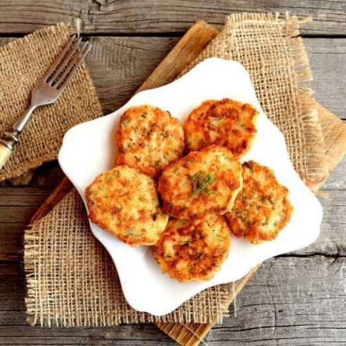 Baked Salmon Croquettes on a white plate sitting on a wooden table
