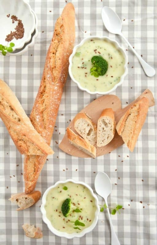 Best Broccoli Soup Recipe - Healthy Broccoli Soup shown in white bowls on table with bread and spoons