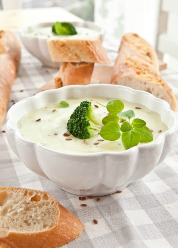 A photo of the best broccoli soup in a white bowl garnished with greens