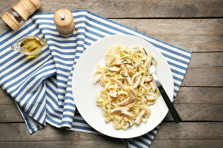 An overhead shot of Easy Chicken Alfredo on a white plate sitting on a wooden surface with a blue and white striped dishcloth