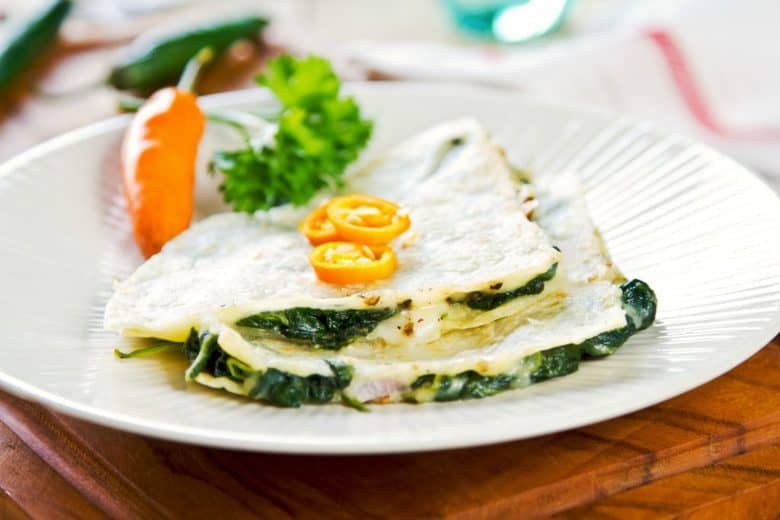 A close up of Spinach Quesadillas on a white plate with chili made from the Easy Spinach Quesadilla on white plate