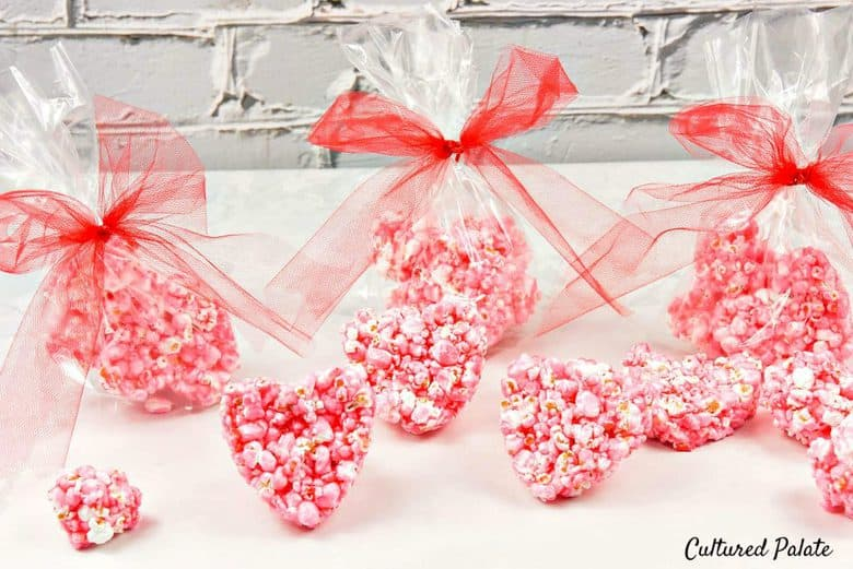 Heart shaped popcorn balls in red wrappers on a white surface