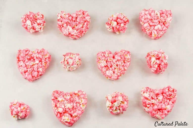 Big and small heart shaped popcorn balls on a white surface made from popcorn balls recipe